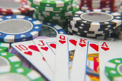 jeux de cartes posé sur une multitude de jetons de casino